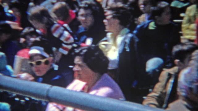 1963: foule assis regardant lycée voie se rencontrent au cours de la journée d'été brillant. - Vidéo