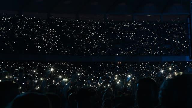 vídeos de stock e filmes b-roll de crowd waving cellphones and flashlights at stadium during rock concert / sports game - atuação