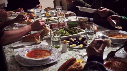 Crowded and hungry muslim family breaking fast in iftar on Ramadan month Crowded and hungry Turkish Muslim family breaking fast in iftar on Ramadan month within joy and happiness with beautiful vegan food on the table middle east stock videos & royalty-free footage