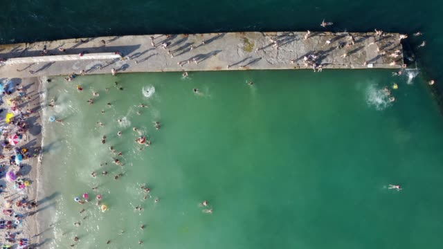 Crowded city beach in high season summer time vacation. Top aerial drone view - video