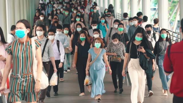 überfüllte menschen, die eine gesichtsmaske tragen, um coronavirus oder covid-19 ausbruch zu verhindern - krankheitsverhinderung stock-videos und b-roll-filmmaterial