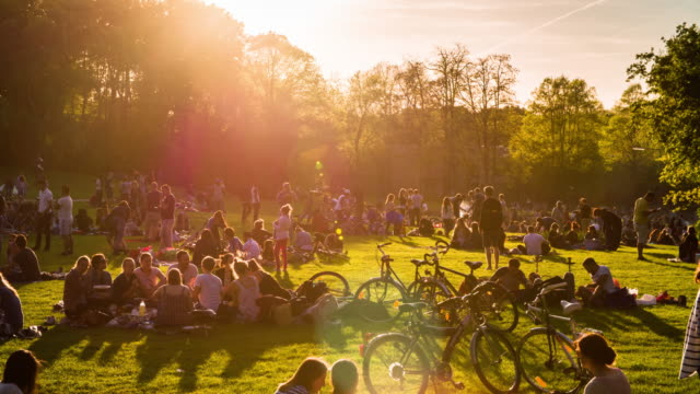 vídeos de stock e filmes b-roll de crowded park in warm sunlight - parque público