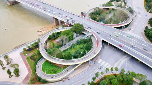 vidéos et rushes de carrefour bondé près de la rivière dans la ville moderne - route surélevée