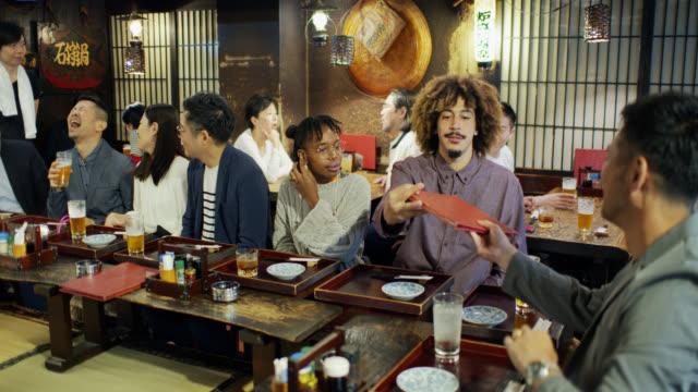 ハッピーアワーの東京バーの混雑 - アフリカ民族点の映像素材/bロール