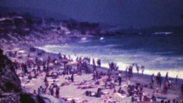 1964: Crowded tourist sunny ocean beach big waves crash on shore. video