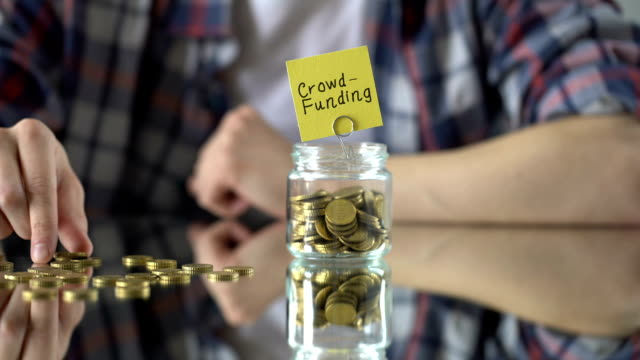 Crowd-funding phrase written above glass jar with money, successful startup