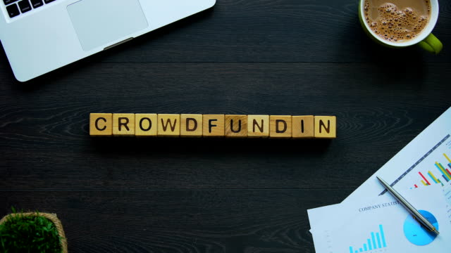 Crowdfunding word made of cubes, collective organization of housing company
