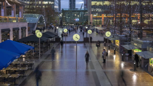 crowds at canary wharf at dusk - clock стоковые видео и кадры b-roll