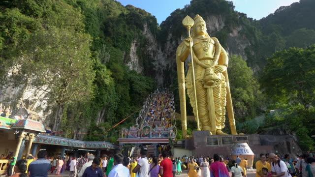 толпы преданных посещают пещеры бату, чтобы помолиться и совершить различные акты преданности в тайпусаме, малайзия - верующий стоковые видео и кадры b-roll