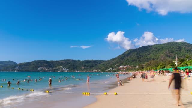 vidéos et rushes de foules de touristes à la plage de patong, destination de voyage célèbre, phuket, thaïlande; zoom arrière - time lapse - mer d'andaman