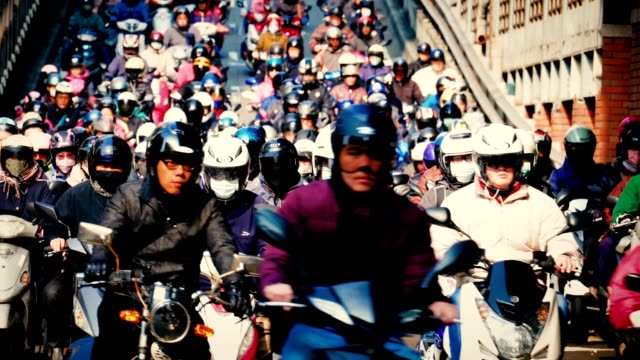 Crowed of people are riding scooters, Traffic on the bridge through city