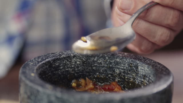 Cruching Spices and Herbs in Mortar and Pestle video