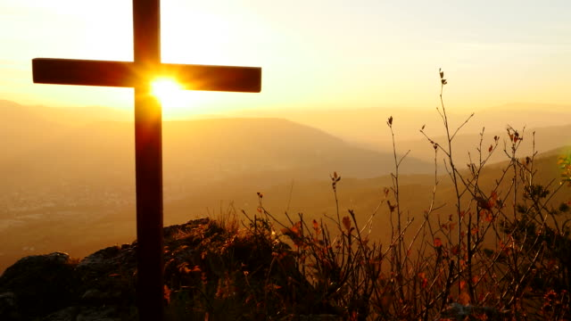 Crucifix on Mountain during Sunset. Beautiful Nature and Calm Atmosphere.