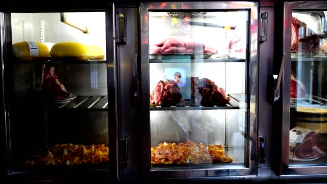 Crude meat in refrigerators. Shooting in cafe. La Coruña, Spain. Demonstration to visitors of products from which dishes prepare. fridge stock videos & royalty-free footage