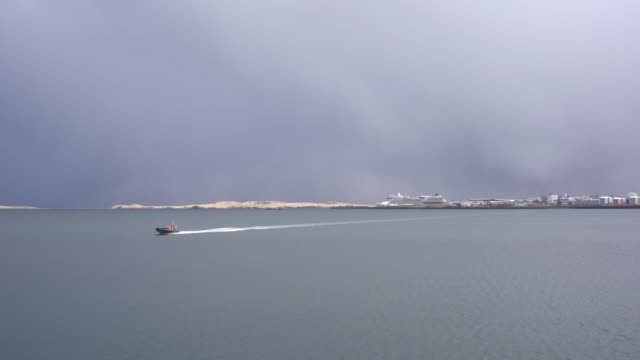 Cruise liner moored in the port of Reykjavik, the capital of Iceland. A motor boat swims quickly through the sea.
