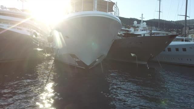 vídeos de stock, filmes e b-roll de cruzeiro perto passado arcos grande iate ao pôr do sol - marina