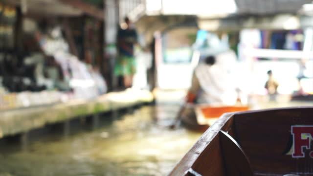 Cruising on paddle boat at Damnoen Saduak Floating Market in Ratchaburi, Thailand. No face and blur atmosphere video