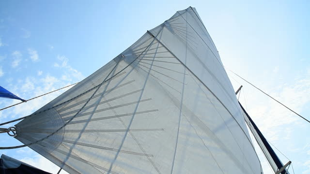 HD: Cruising Sail In The Wind HD1080p: Low angle shot of a jib sail on a sailing boat with the cloudy sky in the background. yachting stock videos & royalty-free footage
