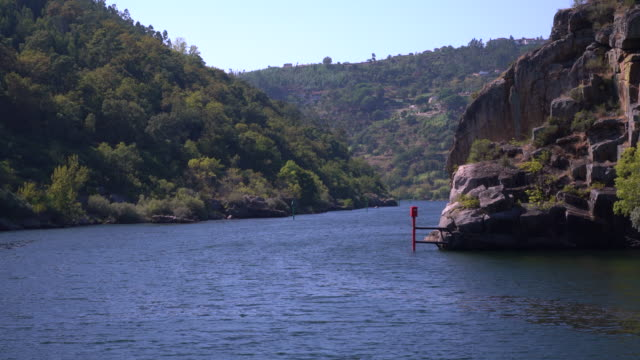 Cruising through narrow gorge or canyon on the Douro river near the Carrapatelo dam in northern Portugal - video