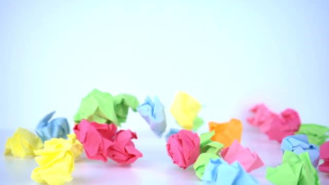 vídeos de stock e filmes b-roll de crumpled colorful paper falling in slow motion. - amarrotado