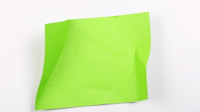 vídeos de stock e filmes b-roll de crumpled paper on green background, stop motion animation - triturar atividade