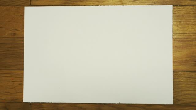 vídeos de stock e filmes b-roll de crumpled piece of white paper. stop motion animation. - amarrotado