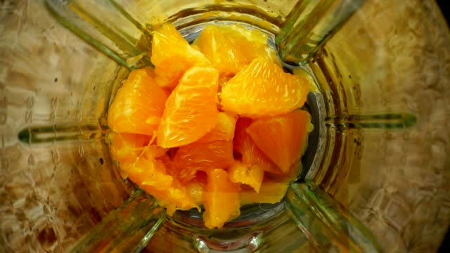 crushing of orange in the blender. slow motion.preparation of smoothie in the blender. top view. - healthy green juice video stock e b–roll