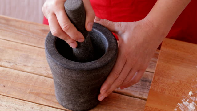 Crushing spices using mortar and pestle Home cooking - crushing spices using solid stone mortar and pestle, close up mortar and pestle stock videos & royalty-free footage
