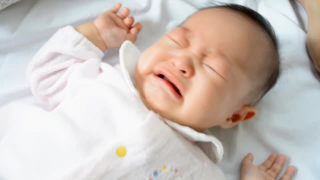 Crying Asian baby girl lying on bed video