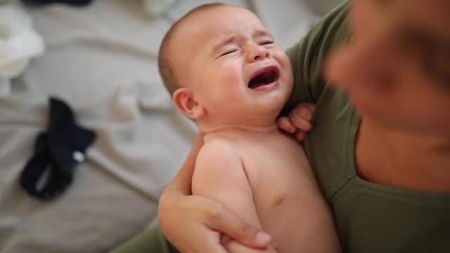 bambino che piange tra le braccia della madre - strillare video stock e b–roll