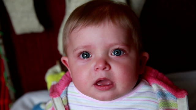 Crying baby suddenly stop crying and stares at camera video