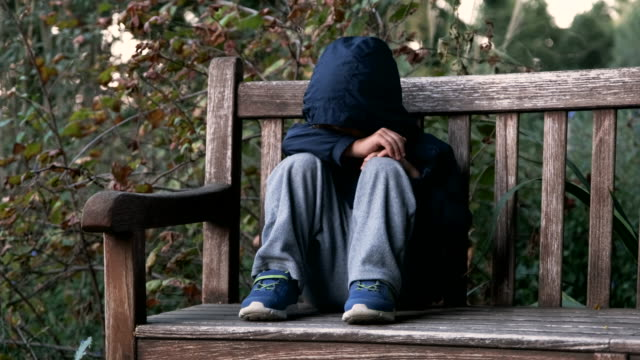 Crying child boy sitting on a bench covering his face