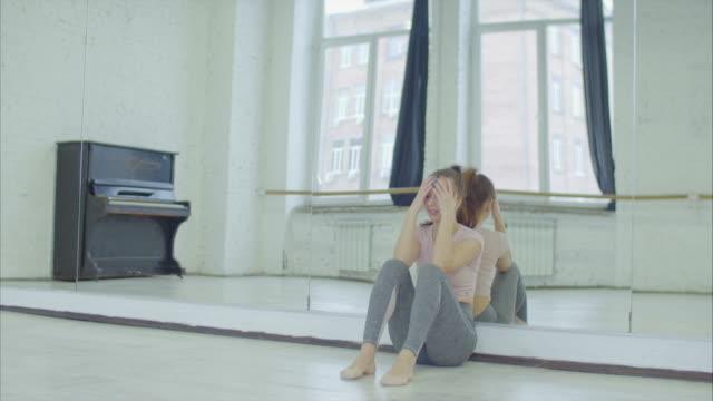 vídeos de stock, filmes e b-roll de chorando a dançarina feminina apoiando-se no espelho em estúdio - bailarina