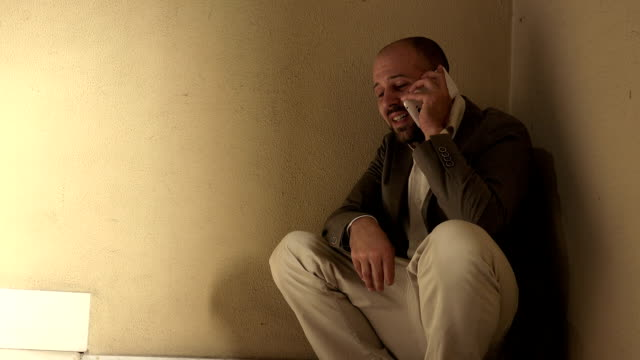 crying man crouching in a corner talking with his smartphone video