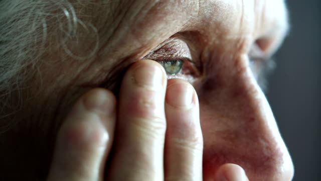 Crying old woman dries her eyes with hand video