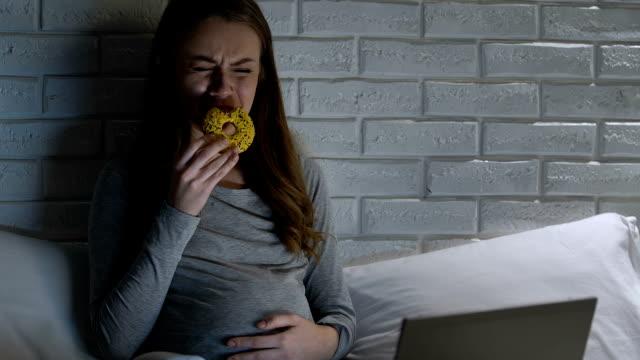 vídeos de stock, filmes e b-roll de fêmea grávida de grito que come a filhós na frente do portátil, desordem das hormonas - gênero humano