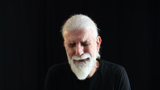 Crying senior man portrait on black background video
