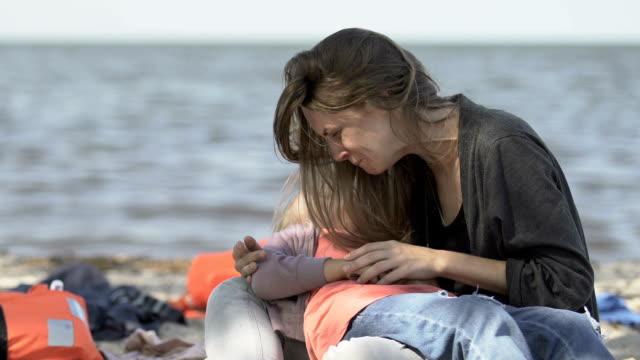 donna piange che tiene in braccio figlia incosciente sulla costa del mare, vittime naufragio - cadavere video stock e b–roll