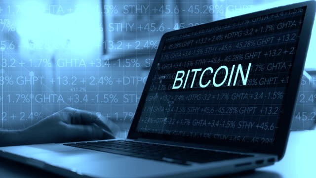 Cryptocurrency concept with stock market ticker scrolling over laptop - Bitcoin