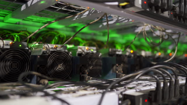Cryptocurrency mining equipment on large farm. ASIC miners on stand racks mine bitcoin in server room. Blockchain techology application specific integrated circuit. Slider camera Cryptocurrency mining equipment on large farm. ASIC miners on stand racks mine bitcoin in server room footage. Blockchain techology application specific integrated circuit footage. television host stock videos & royalty-free footage