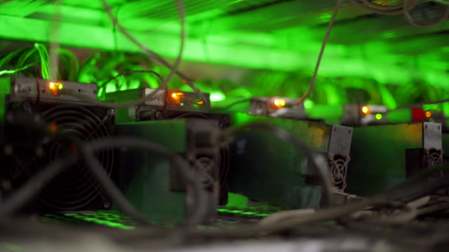 Cryptocurrency mining equipment on large farm. ASIC miners on stand racks mine bitcoin in server room. Blockchain techology application specific integrated circuit. Slider camera