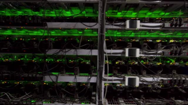 stockvideo's en b-roll-footage met cryptogeld mijnbouw apparatuur op grote boerderij. asic mijnwerkers op stand racks delven bitcoin in serverruimte. blockchain techology applicatie specifieke geïntegreerde circuit. steadycam beelden langs rekken - bitcoin