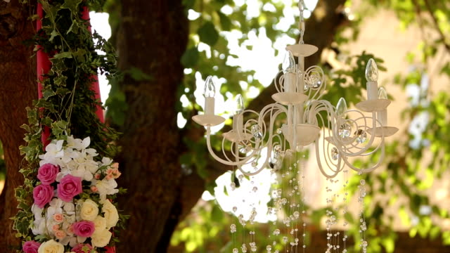 Crystal chandelier with flowers and garlands on wedding ceremony. Holiday decor, rustic style Crystal chandelier with flowers and garlands on wedding ceremony. Holiday stylish decor, rustic style. floral pattern stock videos & royalty-free footage