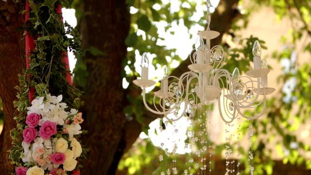 kristallkrona med blommor och kransar på bröllop. holiday inredning, rustik stil - blommönster bildbanksvideor och videomaterial från bakom kulisserna