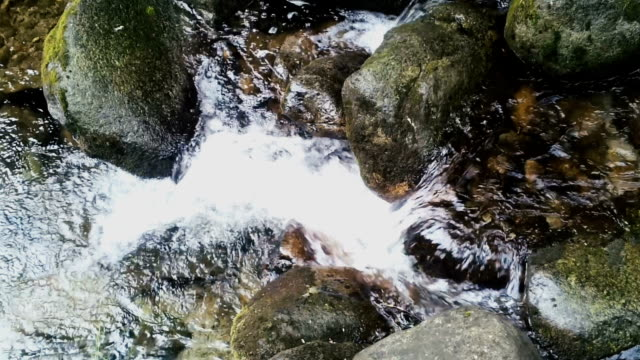 Crystal clear mountain river breaking the boulders stock video footage video