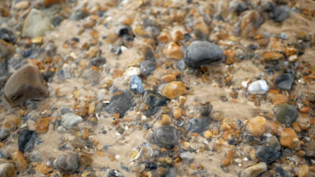 Crystal clear stream flows over the pebbles. Close up