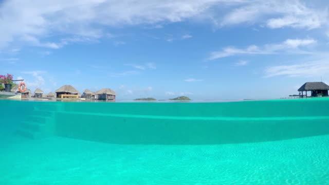 4K UNDERWATER: Crystal clear water in beautiful empty swimming pool in luxury hotel resort. Exotic dreamy honeymoon overwater waterfront villas in the background. video