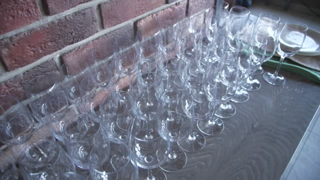 vídeos de stock e filmes b-roll de crystal clear wine glasses on a table against a brick wall - sideboard