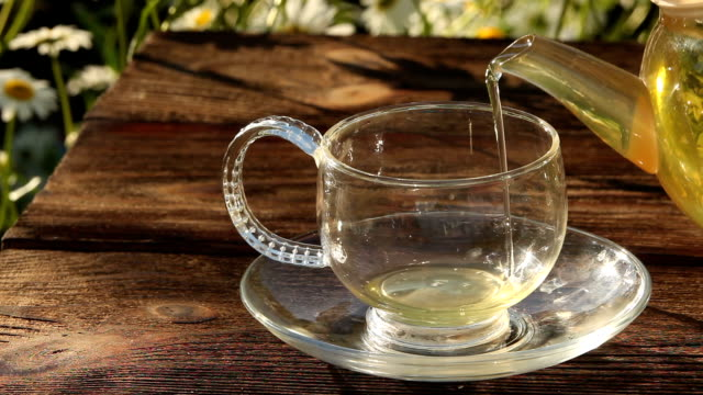 Crystal cup with green tea on table video