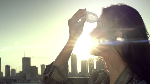 Crystal healing. Woman on a rooftop with city panorama video